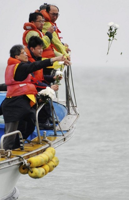 Family members throw flowers in tribute to ferry Sewol sinking victims