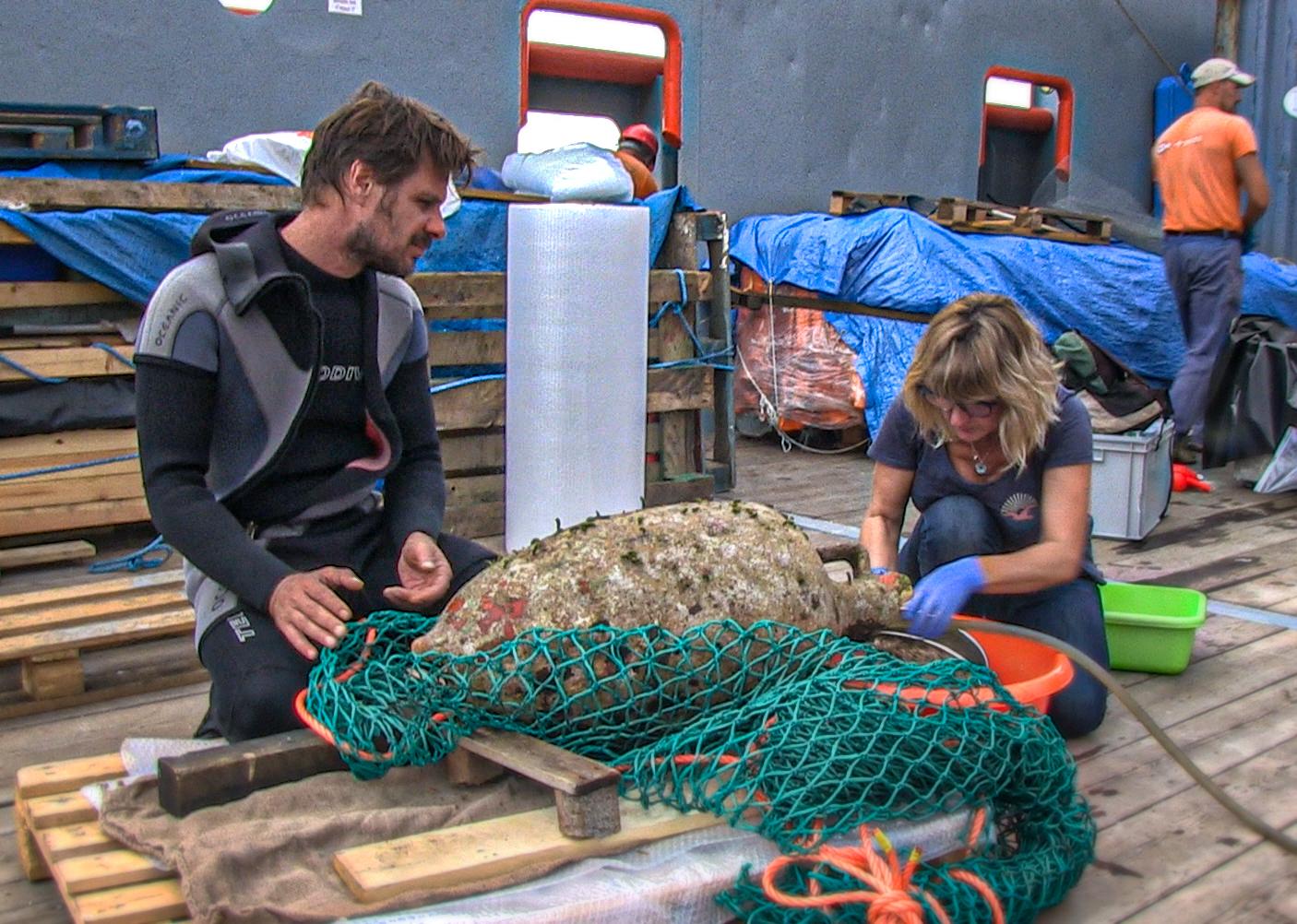 Αμφορέας από το φορτίο του ναυαγίου των Αντικυθήρων στο κατάστρωμα του ερευνητικού πλοίου «ΤΥΦΩΝΑΣ» δέχεται την φροντίδα της προϊσταμένης του τμήματος συντήρησης της Εφορείας Εναλίων Αρχαιοτήτων Χρύσας Φουσέκη και του Δρ Γεώργιου Κουτσουφλάκη